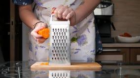 Das Mädchen reibt gekochte Karotten stock video