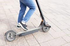 Das Mädchen reitet einen elektrischen Roller, drückt Technologischer umweltfreundlicher Transport Moderner aktiver st?dtischer Le lizenzfreies stockbild