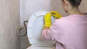 Das Mädchen säubert die Toilette in der Toilette stock video footage