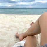 Das Mädchen, das sandige Beine hat, legt auf dem Strand nieder Lizenzfreie Stockfotos