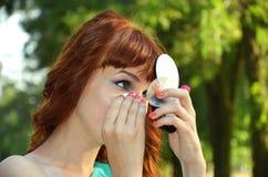 Das Mädchen schaut im Spiegel Lizenzfreies Stockfoto