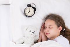 Das Mädchen schläft in einem weißen Bett, unter der Decke nahe bei der Uhr Lizenzfreie Stockbilder