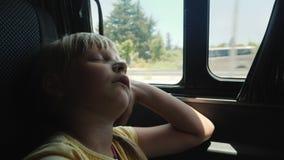 Das Mädchen schläft am Fenster im Rücksitz des Autos Eine langwierige Reise mit einem Kind stock video
