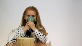 Das Mädchen schließt einen tragbaren Inhalator mit ein und inhaliert die Dämpfe Vorderansicht des Kindes, das eine Maske von eine stock video