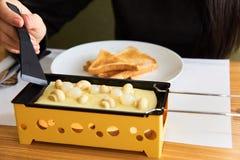 Das Mädchen schmeckt Käse raclette in einem Café Stockfoto