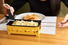 Das Mädchen schmeckt Käse raclette in einem Café Stockfotografie