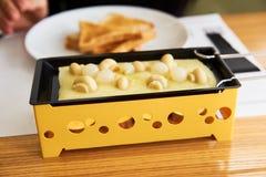 Das Mädchen schmeckt Käse raclette in einem Café Stockbilder