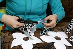 Das Mädchen schnitt Elemente vom selbstklebenden Papier heraus, um die Defekte der weißen Tür zu maskieren Stockbild