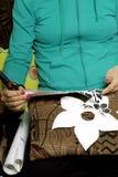 Das Mädchen schnitt Elemente vom selbstklebenden Papier heraus, um die Defekte der weißen Tür zu maskieren Stockfotos