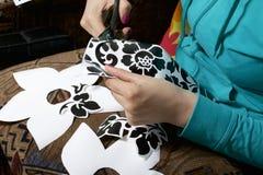 Das Mädchen schnitt Elemente vom selbstklebenden Papier heraus, um die Defekte der weißen Tür zu maskieren Stockfotografie