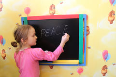 Das Mädchen schreibt auf eine Tafel ein Wort der Frieden Stockbilder