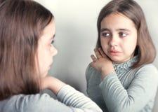 Das Mädchen schreit und betrachtet ihre Reflexion im Spiegel Stockbild