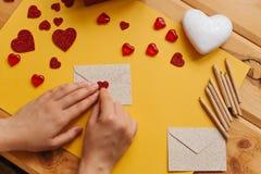 Das Mädchen schrieb einen Brief mit Glückwünschen und klebt den Umschlag mit einem Symbol in Form eines Herzens Nahe gelegene Lüg Stockfotografie