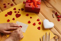 Das Mädchen schrieb einen Brief mit Glückwünschen und klebt den Umschlag mit einem Symbol in Form eines Herzens Nahe gelegene Lüg Stockbild