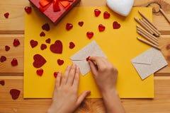 Das Mädchen schrieb einen Brief mit Glückwünschen und klebt den Umschlag mit einem Symbol in Form eines Herzens Nahe gelegene Lüg Stockfotos