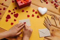 Das Mädchen schrieb einen Brief mit Glückwünschen und klebt den Umschlag mit einem Symbol in Form eines Herzens Nahe gelegene Lüg Lizenzfreies Stockfoto