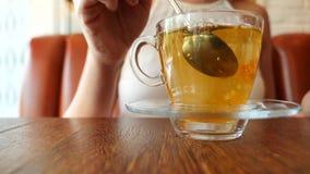 Das Mädchen setzt ein Stück braunen Zucker in einen transparenten Becher mit grünem Tee ein Luftblasen steigen oben Langsame Bewe stock footage