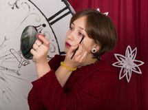 Das Mädchen setzt Make-up auf ihr Augenion der Hintergrund der Uhren des neuen Jahres stockbilder