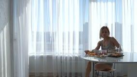 Das Mädchen setzt sich am ausdehnenden und trinkenden Kaffee der Tabelle hin stock footage