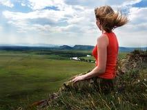 Das Mädchen sitzt auf dem Berg und untersucht den Abstand Lizenzfreies Stockfoto
