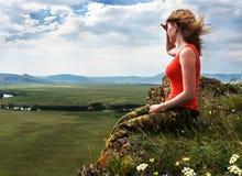 Das Mädchen sitzt auf dem Berg und untersucht den Abstand Lizenzfreies Stockbild