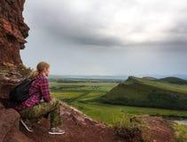 Das Mädchen sitzt auf dem Berg und untersucht den Abstand Stockfotos