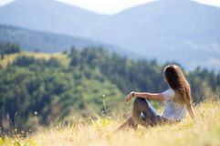 Das Mädchen sitzt auf dem Bergabhang Lizenzfreies Stockfoto
