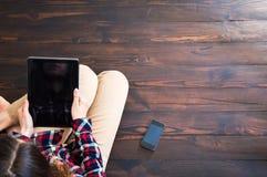 Das M?dchen sitzt auf dem Bretterboden und liest die Nachrichten in der Tablette von der Spitze lizenzfreie stockbilder