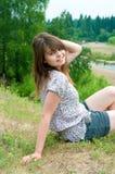 Das Mädchen sitzt auf dem Felsen Stockfoto
