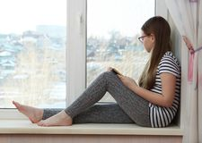 Das Mädchen sitzt auf dem Fensterbrett und schaut heraus das Fenster Stockfotografie
