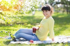 Das Mädchen sitzt auf dem Gras und hält ein Glas Saft stockbild