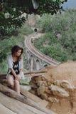 Das Mädchen sitzt auf dem Hintergrund der Brücke Lizenzfreie Stockfotografie