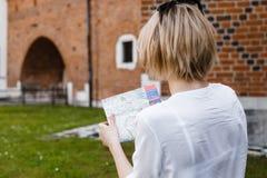Das Mädchen sitzt auf dem Rasen eine junge Frau in grüne Gärten Stilvolles Damenlächeln Tourist mit einer Karte von Einheimischen stockfotos