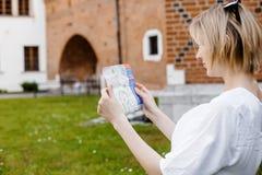 Das Mädchen sitzt auf dem Rasen eine junge Frau in grüne Gärten Stilvolles Damenlächeln Tourist mit einer Karte von Einheimischen lizenzfreie stockfotos