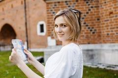 Das Mädchen sitzt auf dem Rasen eine junge Frau in grüne Gärten Stilvolles Damenlächeln Tourist mit einer Karte von Einheimischen lizenzfreie stockfotografie