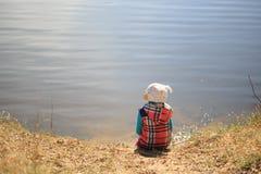 Das Mädchen sitzt auf dem Ufer und den Träumen Lizenzfreies Stockfoto