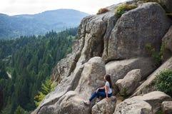 Das Mädchen sitzt auf den Felsen Lizenzfreies Stockfoto
