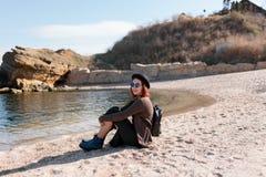 Das Mädchen sitzt auf der Küste Lizenzfreies Stockfoto