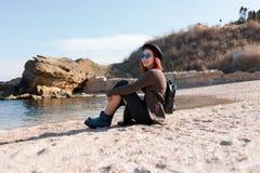 Das Mädchen sitzt auf der Küste Stockbilder