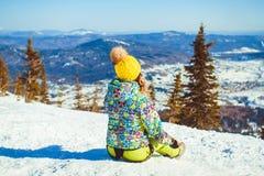 Das Mädchen sitzt auf die Oberseite im Winter Lizenzfreie Stockfotos
