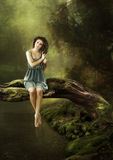 Das Mädchen sitzt auf einem Baum über dem Wasser Stockfoto