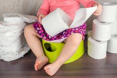 Das Mädchen sitzt auf einem grünen Topf und lernt die grundlegende Hygiene und schaltet von den Windeln zu einer Toilette stockfotografie