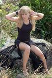Das Mädchen sitzt auf einem großen Felsen Stockfoto