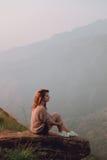 Das Mädchen sitzt auf einem Stein mit Blick auf die Berge Lizenzfreie Stockfotografie