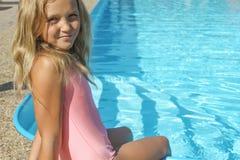 Das Mädchen sitzt durch das Pool Lizenzfreies Stockfoto