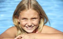 Das Mädchen sitzt durch das Pool Stockfotografie