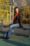 Das Mädchen sitzt an einer Bushaltestelle lizenzfreies stockbild