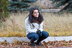 Das Mädchen sitzt in einer Jacke im Herbst im Park Stockbilder