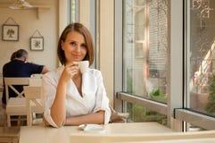 Das Mädchen sitzt im Kaffee Stockbilder