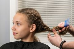 Das Mädchen sitzt am Meister auf hairdresses, tut ein Stapeln stockbilder